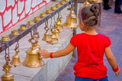 POKHARA, NÉPAL LE 10 OCTOBRE 2017 : Belle petite fille touchant les cloches de la taille différente accrochant dans Taal Barahi Photo stock