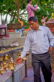 POKHARA, NÉPAL LE 10 OCTOBRE 2017 : Homme d'affaires non identifié touchant les cloches de la taille différente accrochant dans T Images stock