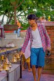 POKHARA, NÉPAL LE 10 OCTOBRE 2017 : Jeune homme non identifié touchant les cloches de la taille différente accrochant dans Taal B Photo stock