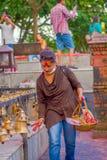 POKHARA, NÉPAL LE 10 OCTOBRE 2017 : Jeune homme non identifié touchant les cloches de la taille différente accrochant dans Taal B Photographie stock libre de droits