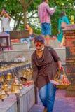 POKHARA, NÉPAL LE 10 OCTOBRE 2017 : Jeune homme non identifié touchant les cloches de la taille différente accrochant dans Taal B Image stock