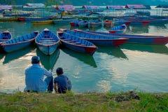 Pokhara, Népal - 4 septembre 2017 : Père et fils s'asseyant dans l'au bord du lac appréciant la vue des bateaux dans le lac Photo stock