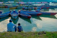 Pokhara, Népal - 4 septembre 2017 : Père et fils s'asseyant dans l'au bord du lac appréciant la vue des bateaux dans le lac Images libres de droits