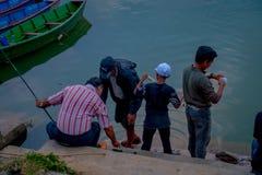 Pokhara, Népal - 4 septembre 2017 : Personnes non identifiées pêchant dans au bord du lac avec quelques bateaux dans le lac de ph Photo libre de droits