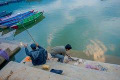 Pokhara, Népal - 4 septembre 2017 : Personnes non identifiées pêchant dans au bord du lac avec quelques bateaux dans le lac de ph Image stock