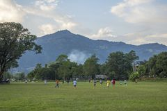 Boys and men playing football on the green grass in the countryside against the backdrop of the stock photography