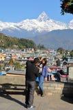 POKHARA, NEPAL - 9 DE ENERO DE 2015: Un par de turistas con Machapuchare enarbolan en el fondo Imágenes de archivo libres de regalías