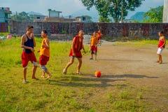 POKHARA, NEPAL - 6 DE OCTUBRE DE 2017: Adolescente no identificado del monje budista que juega a fútbol en el monasterio de Sakya Foto de archivo libre de regalías