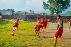 POKHARA, NEPAL - 6 DE OCTUBRE DE 2017: Adolescente no identificado del monje budista que juega a fútbol en el monasterio de Sakya Fotografía de archivo libre de regalías