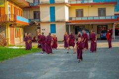POKHARA, NEPAL - 6 DE OCTUBRE DE 2017: Adolescentes no identificados del monje budista que disfrutan del tiempo libre en un patio Foto de archivo libre de regalías
