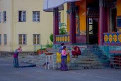 POKHARA, NEPAL - 6 DE OCTUBRE DE 2017: Gente no identificada que da une vuelta y un adolescente del monje budista que se sienta e Imagenes de archivo