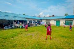 POKHARA, NEPAL - 6 DE OCTUBRE DE 2017: Niños no identificados que juegan a fútbol en un patio trasero y que llevan los uniformes, Imagen de archivo