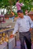 POKHARA, NEPAL 10 DE OUTUBRO DE 2017: Homem de negócios não identificado que toca nos sinos do tamanho diferente que penduram em  Imagens de Stock