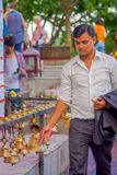 POKHARA, NEPAL 10 DE OUTUBRO DE 2017: Homem de negócios não identificado que toca nos sinos do tamanho diferente que penduram em  Fotos de Stock Royalty Free