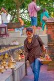 POKHARA, NEPAL 10 DE OUTUBRO DE 2017: Homem novo não identificado que toca nos sinos do tamanho diferente que penduram em Taal Ba Imagem de Stock