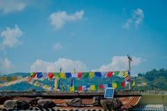POKHARA, NEPAL - 6 DE OUTUBRO DE 2017: Vista exterior bonita de bandeiras coloridas sobre raizes de uma construção, em Pokhara, N imagens de stock royalty free