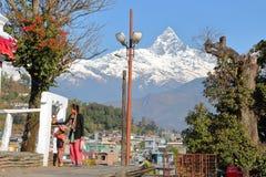 POKHARA, NEPAL - JANUARI 9, 2015: Een Nepalese vrouw met haar zoon die een klok bellen bij de bergen van de Tempelhimalayagebergt Stock Fotografie