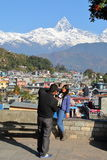 POKHARA, NEPAL - JANUARY 9, 2015: A couple of tourists with Machapuchare Peak in the background Royalty Free Stock Images
