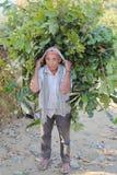 POKHARA, NEPAL - JANUARY 5, 2015: Nepalese man carrying green food load on his back near Pokhara Stock Image