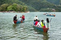 Pokhara, Nepal - July 25, 2011: Tourists enjoy boat ride in vast Phewa Lake, natural colors. Phewa lake is a tourist spot located Royalty Free Stock Images