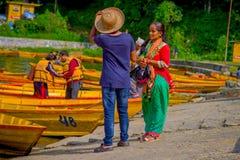 POKHARA NEPAL, LISTOPAD, - 04, 2017: Niezidentyfikowana kobieta opowiada z turystycznym przewdonikiem z niektóre łodziami wewnątr Fotografia Stock