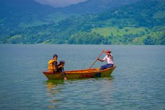 POKHARA NEPAL, LISTOPAD, - 04, 2017: Niezidentyfikowana para cieszy się widok z turystycznym przewdonikiem paddling łódź w Zdjęcia Stock