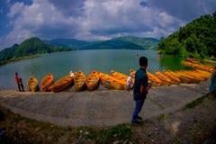POKHARA NEPAL, LISTOPAD, - 04, 2017: Niezidentyfikowani ludzie w granicie jezioro z drewnianymi łodziami przy Begnas z rzędu Zdjęcie Stock