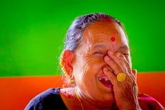 POKHARA NEPAL, LISTOPAD, - 04, 2017: Portret pozuje dla kamery w Pokhara stara kobieta, Nepal, w pomarańcze i zieleni Obrazy Royalty Free