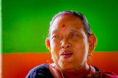 POKHARA NEPAL, LISTOPAD, - 04, 2017: Portret pozuje dla kamery w Pokhara stara kobieta, Nepal, w pomarańcze i zieleni Zdjęcie Stock