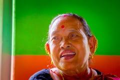POKHARA NEPAL, LISTOPAD, - 04, 2017: Portret pozuje dla kamery w Pokhara stara kobieta, Nepal, w pomarańcze i zieleni Zdjęcia Stock