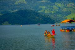 POKHARA NEPAL, LISTOPAD, - 04, 2017: Rodzinny cieszyć się piękny dzień nad żółtą łodzią, staranny spławowa struktura Zdjęcia Stock
