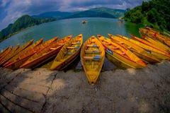 POKHARA NEPAL, LISTOPAD, - 04, 2017: Zamyka up drewniane żółte łodzie z rzędu przy Begnas jeziorem w Pokhara, Nepal, rybi oko Zdjęcie Stock