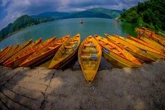 POKHARA NEPAL, LISTOPAD, - 04, 2017: Zamyka up drewniane żółte łodzie z rzędu przy Begnas jeziorem w Pokhara, Nepal, rybi oko Fotografia Stock