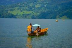 POKHARA, NEPAL - NOVEMBER 04, 2017: Het schitterende familie genieten van van een mooie dag over een gele boot bij Begnas-meer bi Stock Afbeeldingen