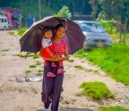 POKHARA NEPAL - NOVEMBER 04, 2017: Oidentifierad kvinna som rymmer en behandla som ett barn i henne armar och skyddar från solen  Royaltyfri Fotografi