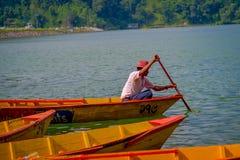 POKHARA, NEPAL - 4. NOVEMBER 2017: Schließen Sie oben oben vom Mann, der das gelbe Boot am Begnas See in Pokhara, Nepal schaufelt Lizenzfreies Stockbild