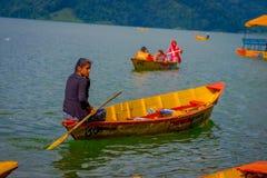 POKHARA, NEPAL - 4. NOVEMBER 2017: Schließen Sie oben oben von der Frau, die das gelbe Boot am Begnas See in Pokhara, Nepal schau Stockbilder