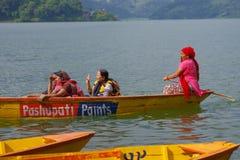 POKHARA, NEPAL - NOVEMBER 04, 2017: Sluit omhoog van het schitterende familie genieten van van een mooie dag over een gele boot i Stock Foto