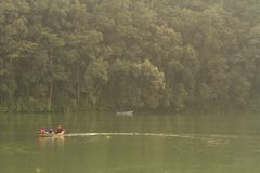 Pokhara, Nepal - November 20, 2015: Tourists row on a boat across Phewa lake royalty free stock photos
