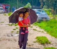 POKHARA, NEPAL - NOVEMBER 04, 2017: Unidentified woman holding a baby in her arms and protecting from the sun using a Royalty Free Stock Photos
