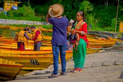 POKHARA, NEPAL - NOVEMBER 04, 2017: Unidentified woman talking with a tourist guide with some boats in at Begnas lake in. Pokhara, Nepal stock photography