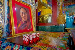 POKHARA, NEPAL - OCTOBER 06 2017: Indoor view of the sanctuary with some oblations and a portrait picture of Dalai Lama. Over a table in Thrangu Tashi Choling Royalty Free Stock Photography