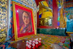 POKHARA, NEPAL - OCTOBER 06 2017: Indoor view of the sanctuary with some oblations and a portrait picture of Dalai Lama. Over a table in Thrangu Tashi Choling Stock Photography