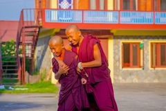 POKHARA, NEPAL - OCTOBER 06 2017: Smiling brothers Buddhist monk boys hugging each other at outside at the Tashi refugee. Settlement in Pokhara, Nepal stock image