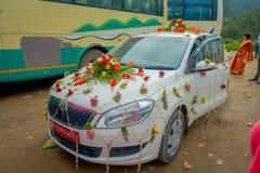 POKHARA NEPAL OKTOBER 10, 2017: Den härliga bilen smyckade med blommor och byinvånare som in firar ett nepalese bröllop Royaltyfri Foto