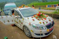 POKHARA NEPAL OKTOBER 10, 2017: Den härliga bilen smyckade med blommor och byinvånare som in firar ett nepalese bröllop Royaltyfria Foton