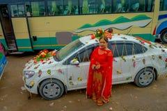 POKHARA NEPAL OKTOBER 10, 2017: Den oidentifierade kvinnan som poserar en ursnygg bil, smyckade nästan med blommor och byinvånare Royaltyfri Fotografi