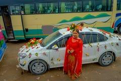 POKHARA NEPAL OKTOBER 10, 2017: Den oidentifierade kvinnan som poserar en ursnygg bil, smyckade nästan med blommor och byinvånare Royaltyfri Bild