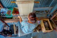 POKHARA NEPAL - OKTOBER 06 2017: Flyg- sikt av den oidentifierade kvinnan som in arbetar på för ullsjal för vävstol fabriks- kläd Arkivfoto