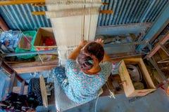 POKHARA NEPAL - OKTOBER 06 2017: Flyg- sikt av den oidentifierade kvinnan som in arbetar på för ullsjal för vävstol fabriks- kläd Arkivfoton